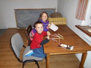 Brother and Sister playing peacefully making paper modes.
